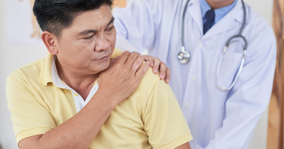 Senior man visiting doctor as he is suffering from shoulder pain