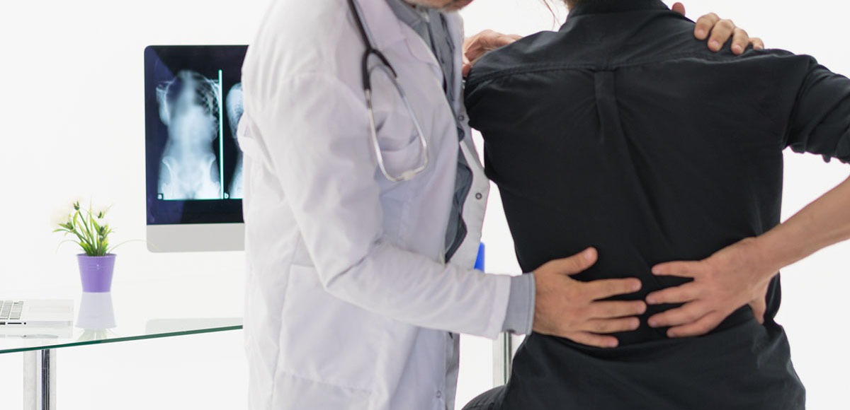 doctor examining a patient who is about to undergo a Minimally Invasive TLIF